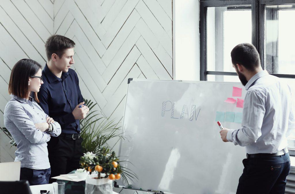 personnes dans un bureau tableau blanc plan